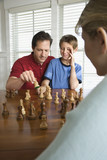 Dad teaching chess to son. poster