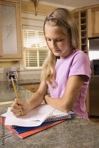 Girl doing homework at kitchen counter.