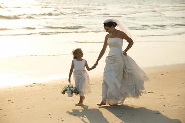 Bride and flower girl walking on beach.