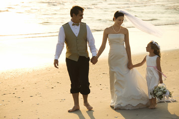 Bride, groom and flower girl walking on beach.