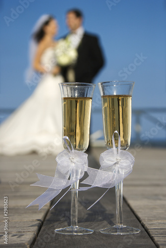 Champagne glasses with bride and groom in background.
