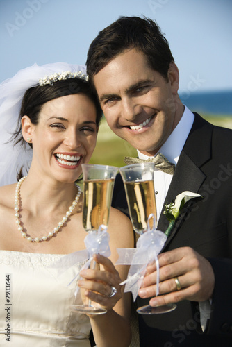 Bride and groom holding champagne glasses.