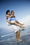 Man carrying woman piggyback at beach. poster