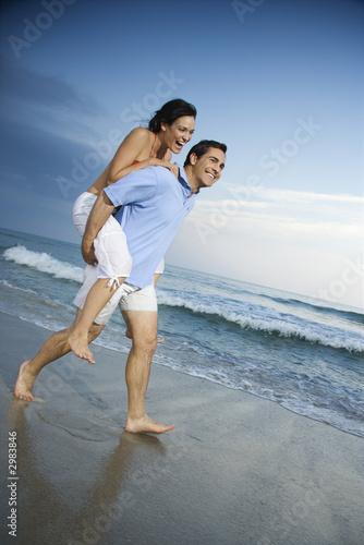 poster of Man carrying woman piggyback at beach.