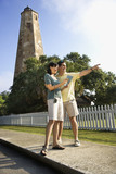Couple sightseeing by lighthouse. poster