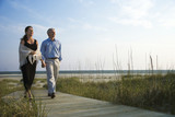 Couple holding hands on coastal walkway.