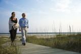 Couple holding hands on coastal walkway. poster