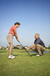Man teaching woman proper golf techniques.
