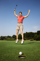 Woman jumping for joy over good golf shot.
