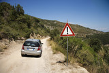 Car heading down dirt road with caution sign. poster