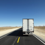 Truck traveling down highway towards horizon. poster
