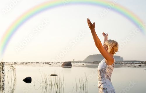 pretty blond raising hands to the rainbow