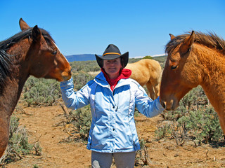 woman with two mustang horses