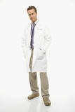 doctor with hands in lab coat pockets. poster