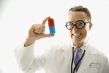 doctor wearing eyeglasses holding an oversized pill. poster