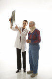 doctor showing x-ray to elderly man in neck brace. poster