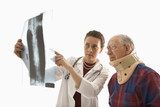 doctor ponting at x-ray with elderly man in neck brace looking o poster