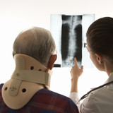 over the shoulders view of doctor pointing at an x-ray as elderl poster