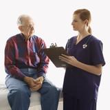 female in scrubs taking notes from elderly man. poster