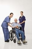 two women wearing scrubs with elderly man in wheelchair. poster