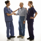 woman in scrubs shaking hand of elderly man with another woman h poster
