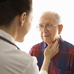 doctor checking an elderly man's pulse.