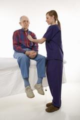 female in scrubs listening to elderly man's heart.
