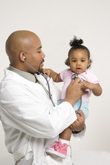 male pediatrician examining baby girl.