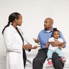 father holding baby talking to pediatrician.
