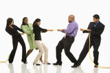 businesswomen playing tug of war against businessmen.