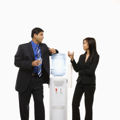 businessman and businesswoman conversing at water cooler.