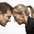 angry man and woman with foreheads together staring at each othe