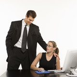 man standing over woman at computer touching her shoulder innapp poster