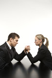 man and woman arm wrestling on table. poster
