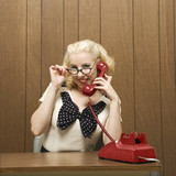 woman dressed in retro outfit holding a red phone. poster