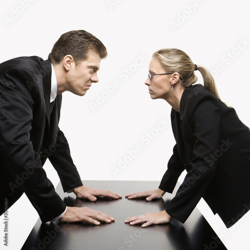 man and woman staring at each other with hostile expressions.