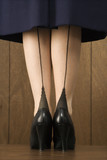 close-up shot of woman in skirt with black heels. poster