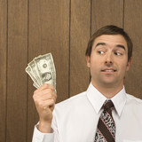 man holding dollar bills and looking towards them. poster