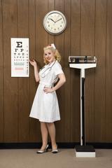 female nurse pointing to eye chart in retro setting.