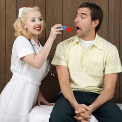 female nurse giving man giant pill.