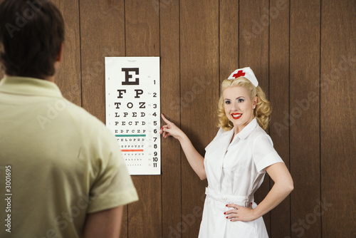 female nurse pointing out eye chart to man.