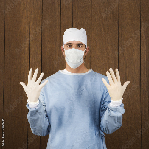 male surgeon wearing mask and gloves.