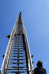 fire ladder extended high with fireman on top