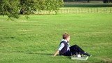 boy sitting relaxing on grass poster