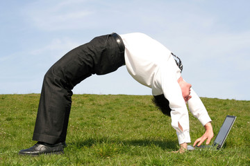 businessman bending over backwards and using lapto