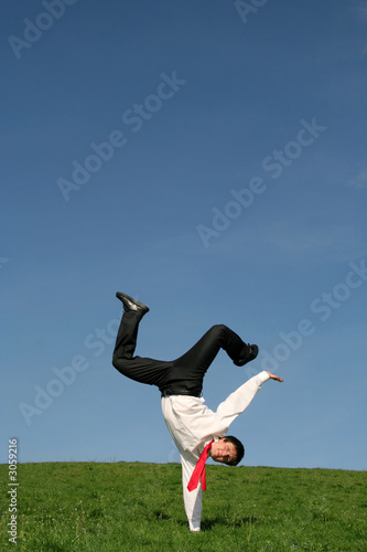 businessman doing one handed handstand outdoors