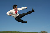 businessman doing a karate kick outdoors