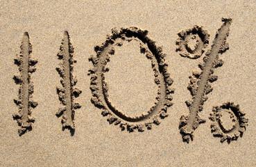 110% written on a sandy beach.