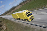 clean yellow truck on highway straight poster