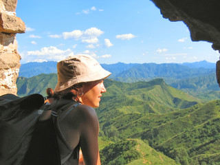 a trekker woman with a hat looking over the mountains and the ju